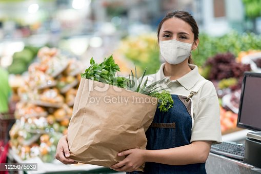 Worker holding a bag of groceries at a food market for and wearing a facemask to avoid the spread of coronavirus – COVID-19 lifestyle concepts