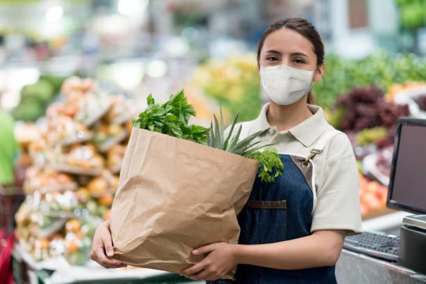 Arbeiter hält eine Tüte Lebensmittel auf einem Lebensmittelmarkt für und trägt eine Gesichtsmaske – Foto