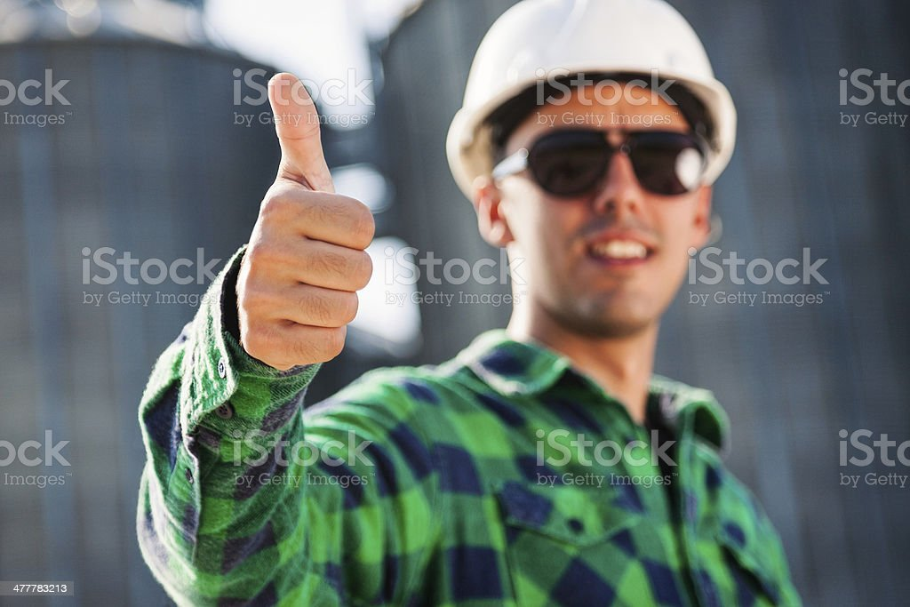 Worker holding blueprints and showing thumbs up royalty-free stock photo