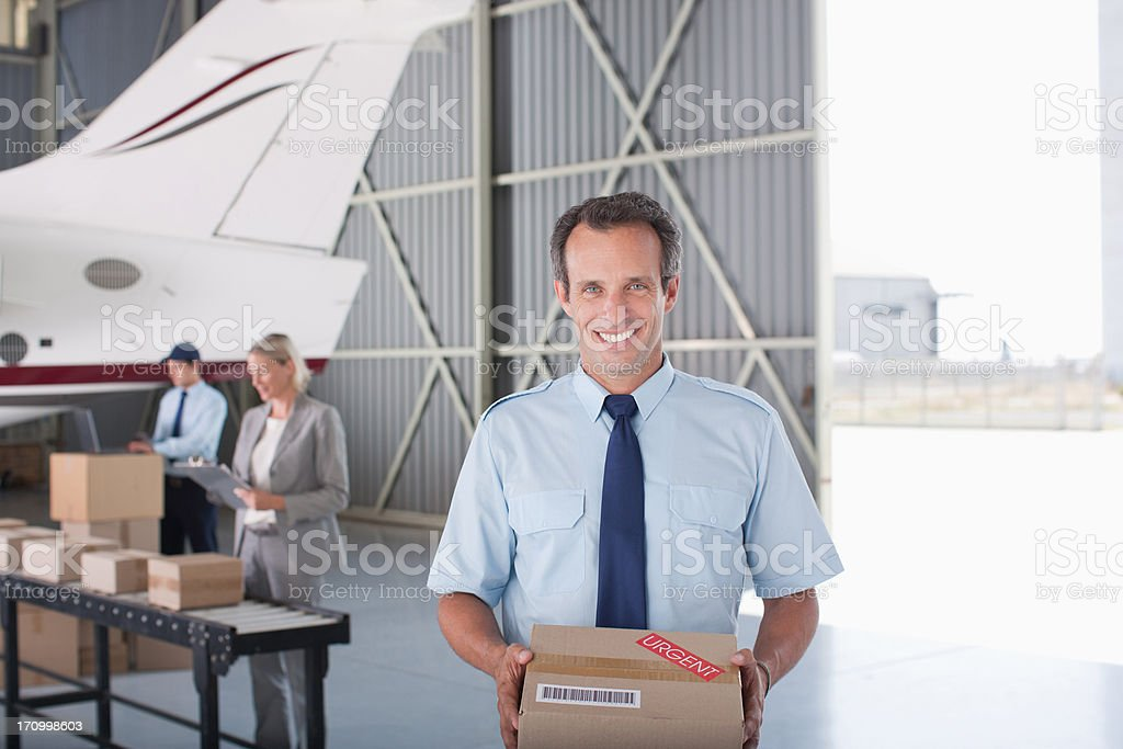 Worker holding box in hangar royalty-free stock photo