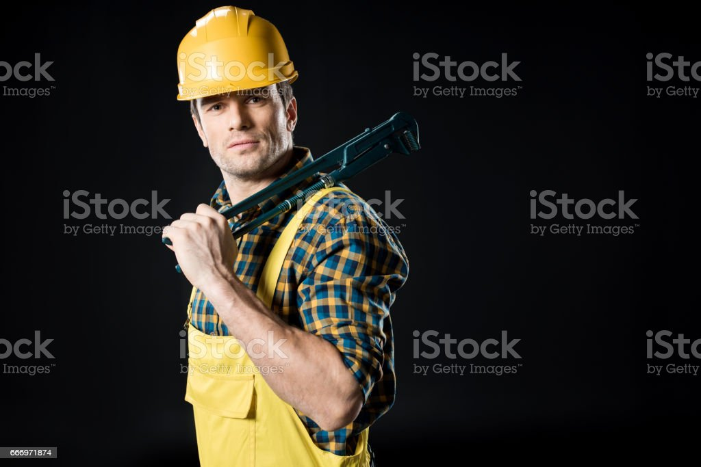 Worker holding pipe wrench stock photo