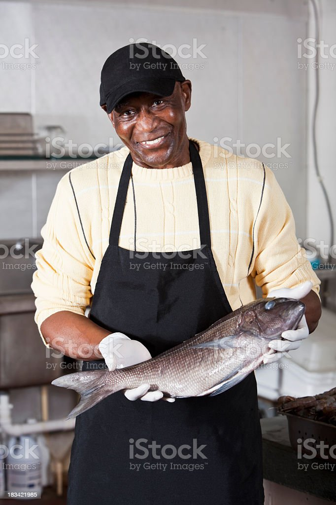 Worker holding seabass in fish market royalty-free stock photo