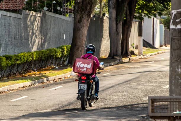 worker ifood on the motorcycle delivers food stock photo