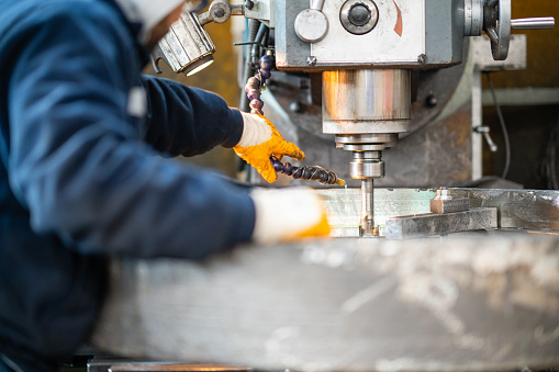 A worker in a factory working on a traditional milling machine