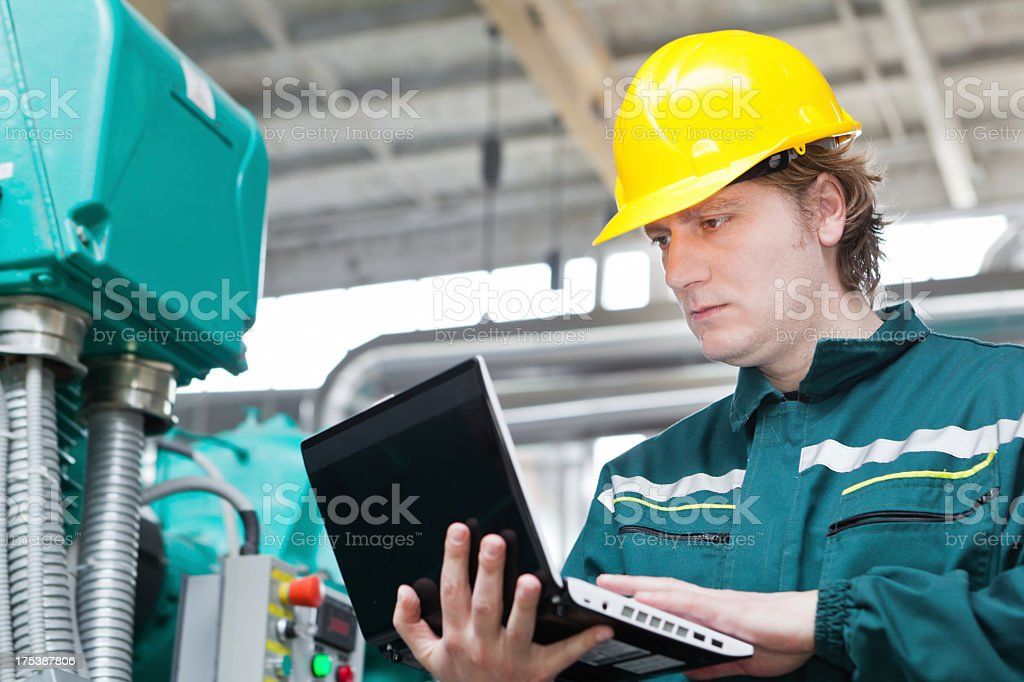 A Worker in a hard hat using a laptop in a heating plant stock photo