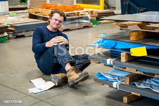 An industrial safety topic. A worker in a manufacturing plant injuring his knee on a piece of sheet metal.