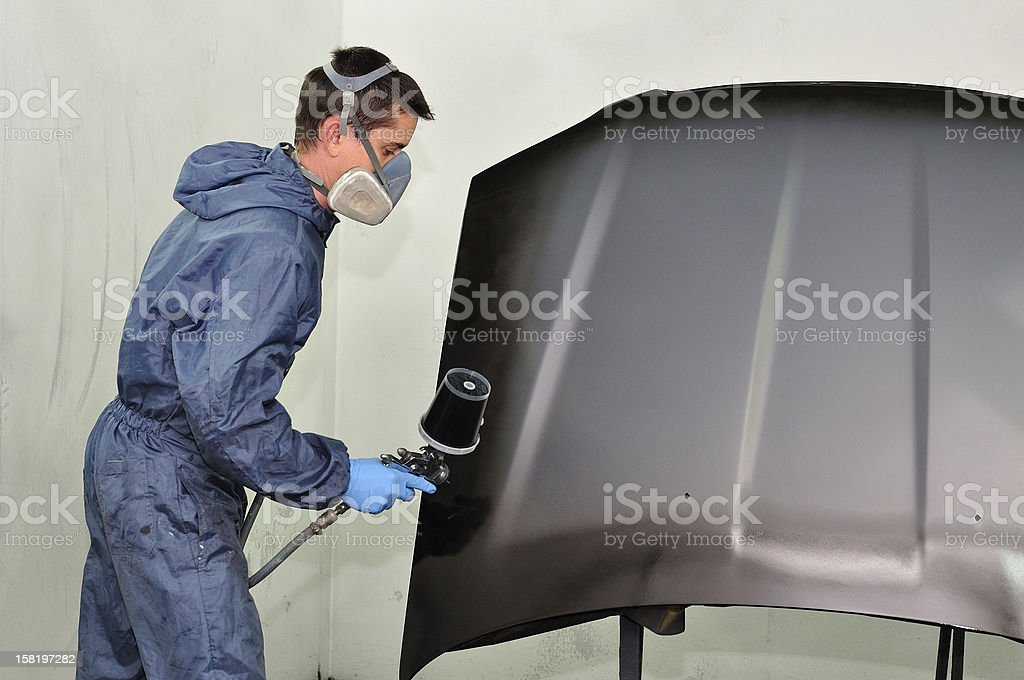 Worker in a paint booth. stock photo
