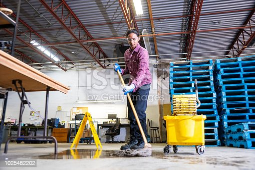 A male worker wearing work boots in a warehouse cleaning up a liquid spill on the floor.