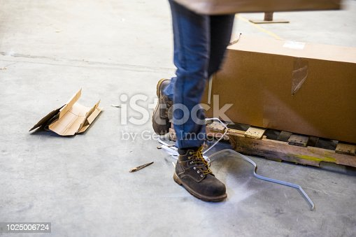 A male worker wearing work boots carrying a box in a warehouse tripping over a dangerous broken pallet and garbage.