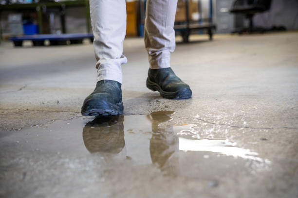 a worker in a warehouse walking in spilled liquid. - danger stock pictures, royalty-free photos & images