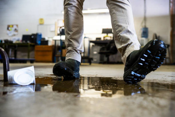 A worker in a warehouse walking in spilled liquid. stock photo