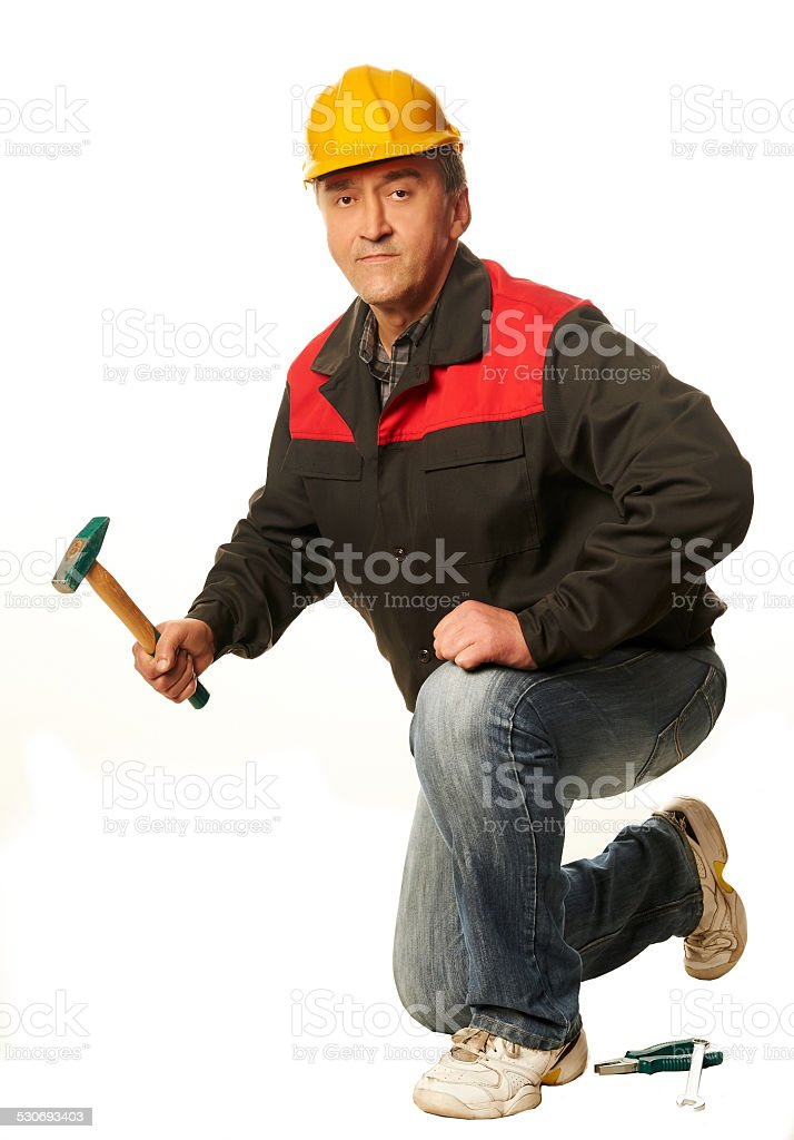 Worker in a yellow hard hat crouched with a hammer stock photo