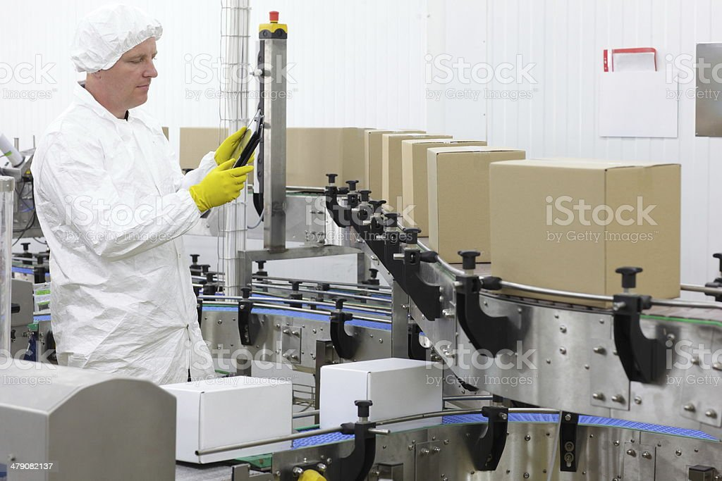 worker in apron with tablet, at production line in factory stock photo