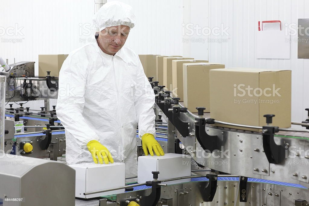 worker in apron, yellow gloves at production line in factory stock photo