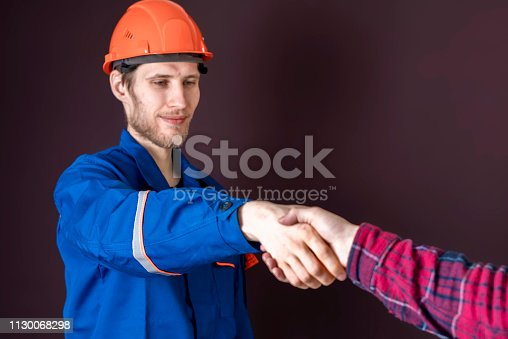 1055059750istockphoto worker in blue uniform having a handshake with his customer b 1130068298