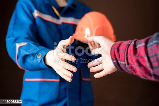 1055059750istockphoto worker in blue uniform having a handshake with his customer b 1130068303