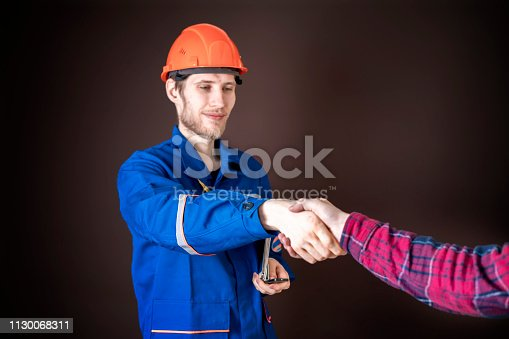 1055059750istockphoto worker in blue uniform having a handshake with his customer b 1130068311