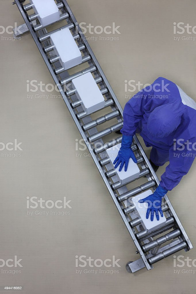 worker in blue uniform working with boxes on conveyor belt stock photo
