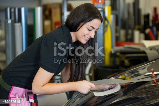 istock Worker in car wrapping workshop glues foil to vehicle 489272619