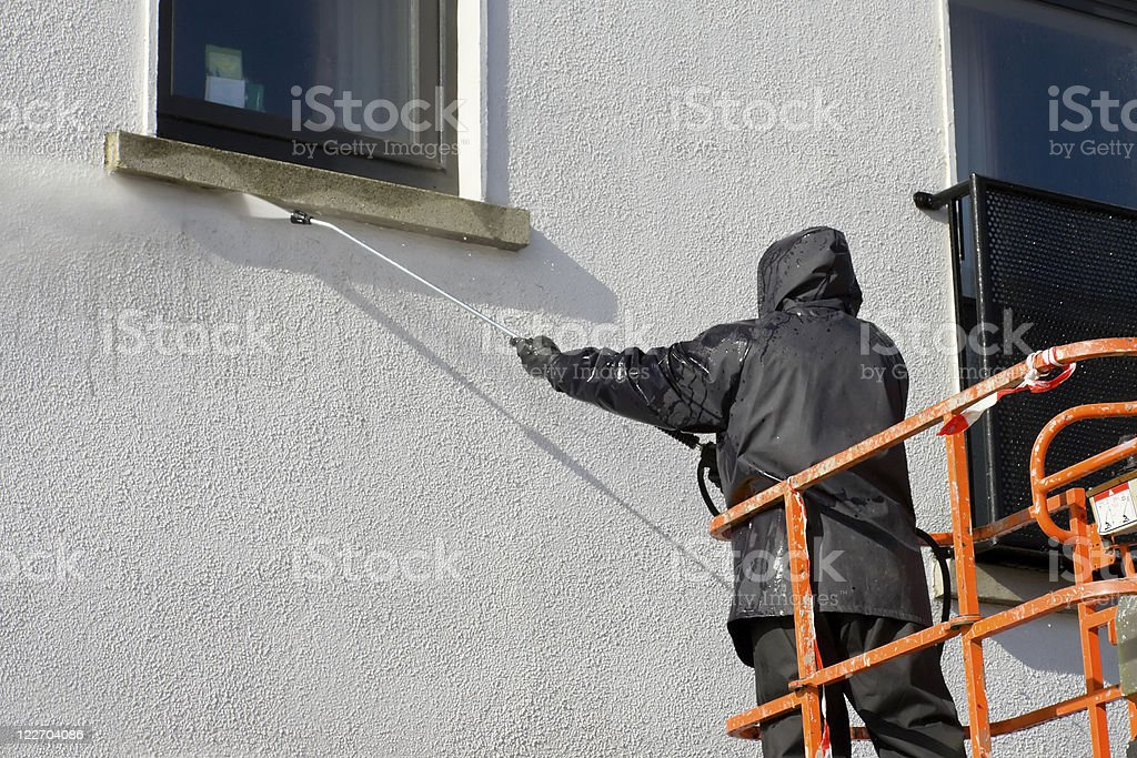 worker in cherry-piker washing a wall stock photo