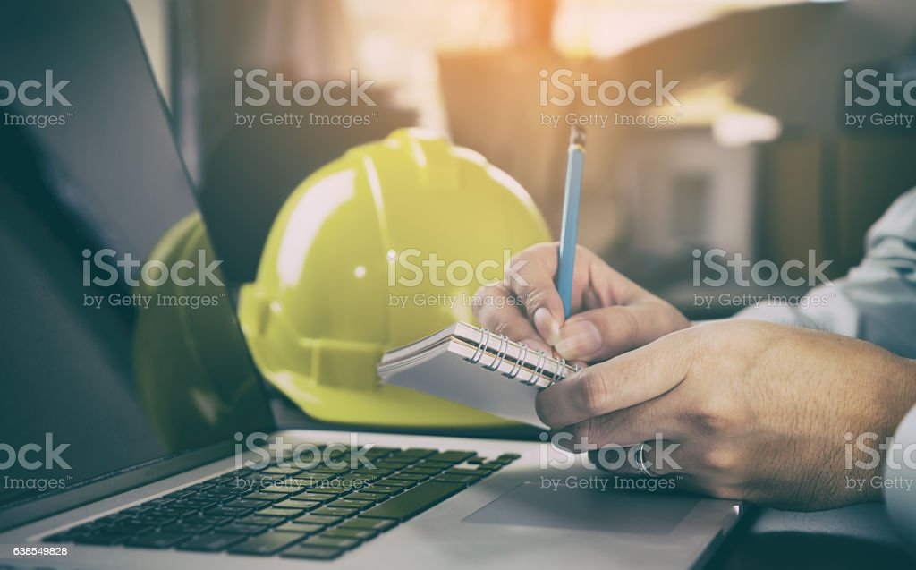 worker in Construction industry is taking note on computer. stock photo