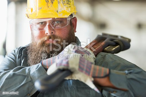 A bearded man working in a metal fabrication plant, carrying a large metal tool on his shoulder.