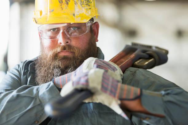 arbeiter in der fabrik mit arbeitsgerät - legere arbeitskleidung stock-fotos und bilder
