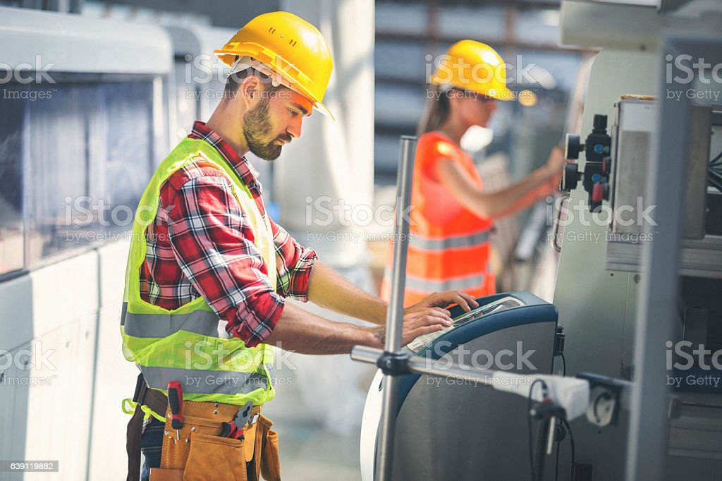 Worker in factory using control panel stock photo