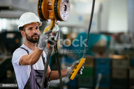 Worker in factory using lifting beam. Shallow DOF. Developed from RAW; retouched with special care and attention; Small amount of grain added for best final impression. 16 bit Adobe RGB color profile.