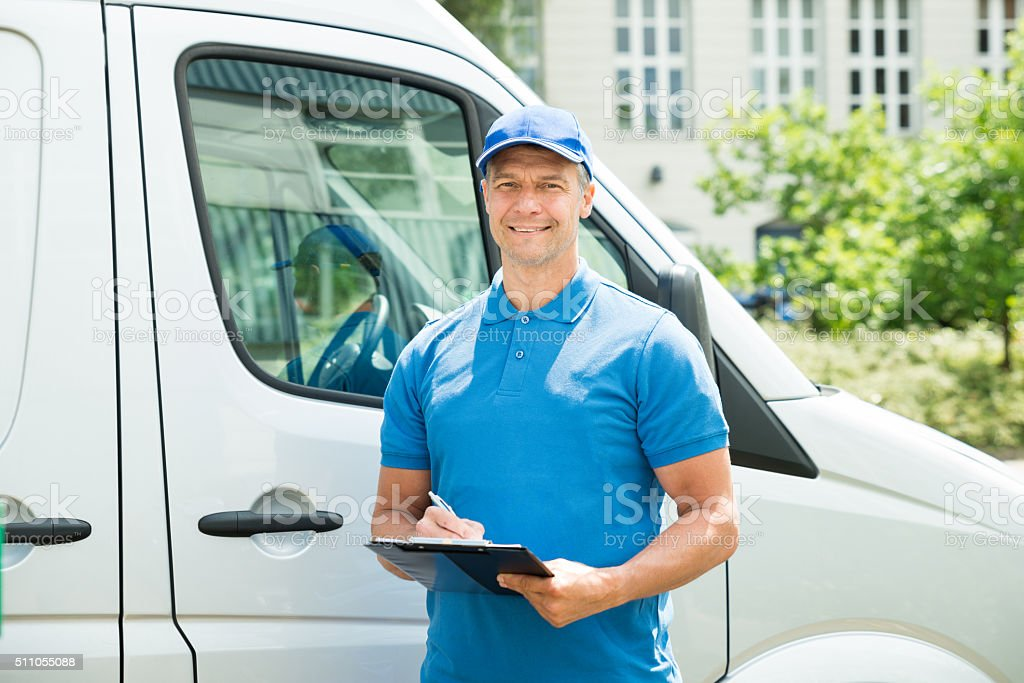 Worker In Front Of Truck Writing On Clipboard stock photo