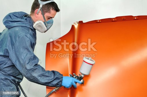 istock Worker in full suit painting a car hood orange 158831655