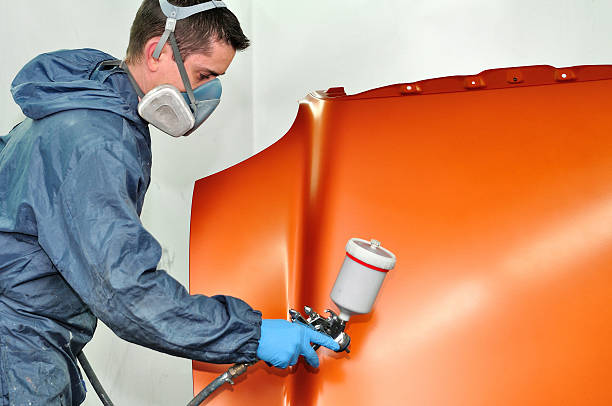 worker in full suit painting a car hood orange - auto body repair stock photos and pictures