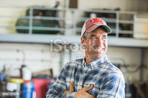 istock Worker in garage wearing trucker's hat 856732928