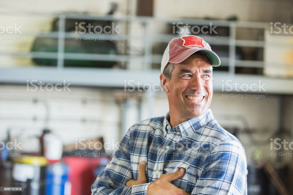 Worker in garage wearing trucker's hat stock photo