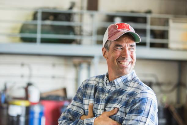 Worker in garage wearing trucker's hat stock photo