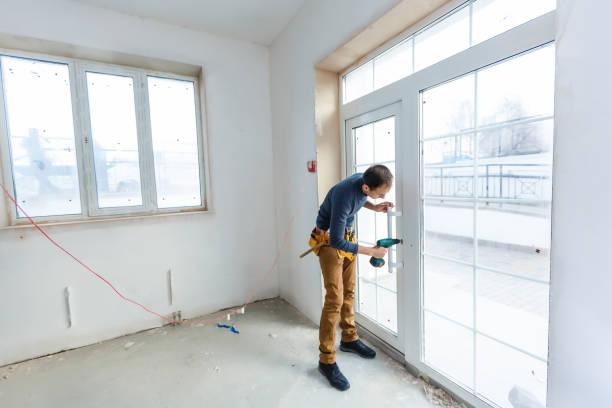 Worker in glazier's workshop, warehouse or storage handling glass stock photo