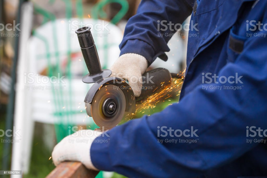 Worker in gloves cutting a steel rail stock photo