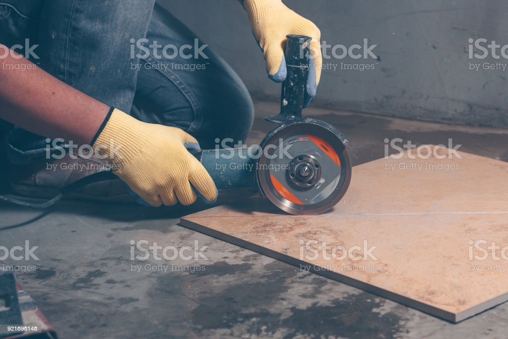 Worker In Gloves Uses Angle Grinder For Cutting Tiles Porcelain