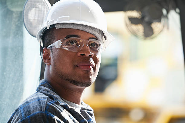Worker in hardhat and safety glasses stock photo