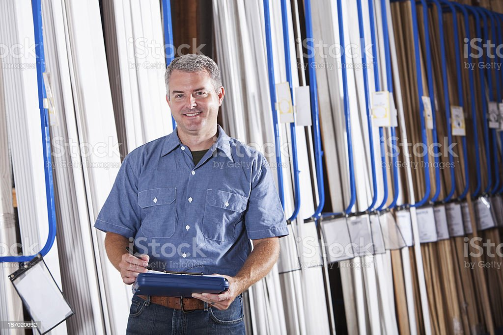 Worker in hardware store taking inventory of moulding stock photo