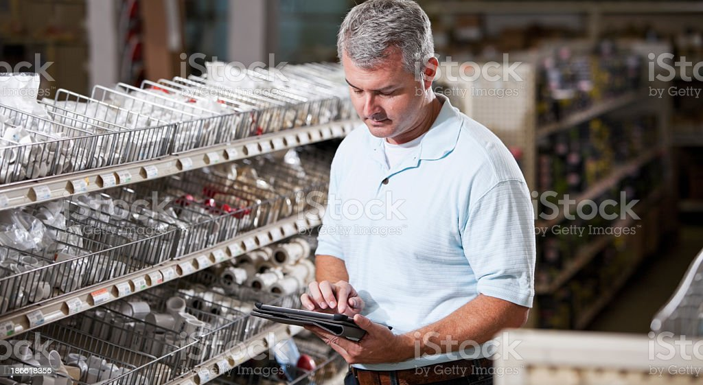 Worker in hardware store taking inventory royalty-free stock photo