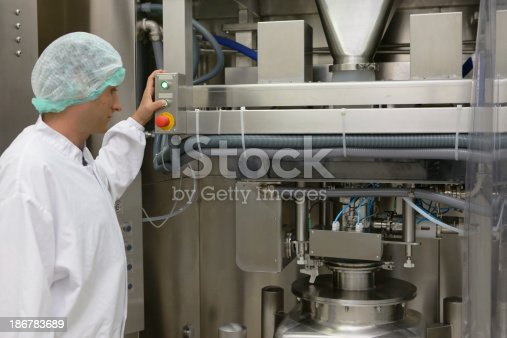 Worker starts machine for making bread