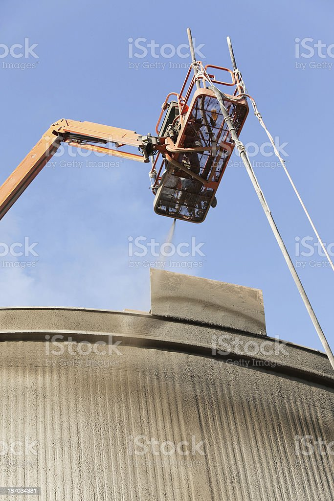 Worker, in Lift Basket, Spraying Shotcrete onto Wall royalty-free stock photo