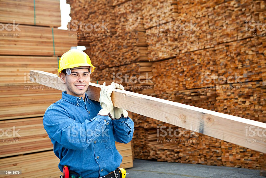 worker in lumber yard carrying 2x4 royalty-free stock photo