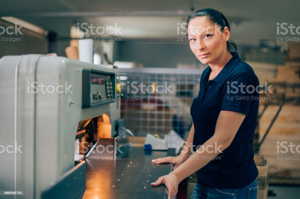 Worker in printing centar uses paper guillotine machine knife stock photo
