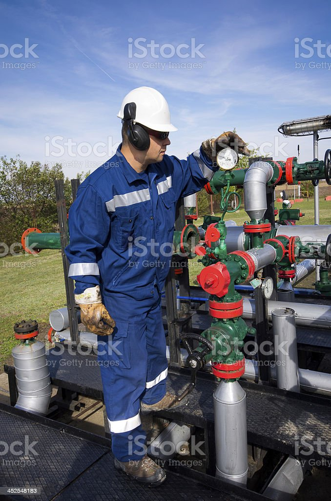 Worker in protective clothes checking the machines stock photo
