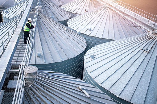 Worker in protective clothes walking grain elevator and observing silos rooftops. Industrial food and grain storage.