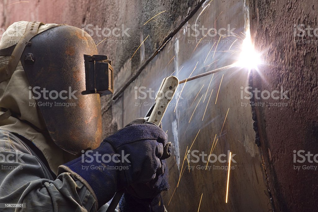 Worker in protective gear welding new plates on ship's hull. stock photo