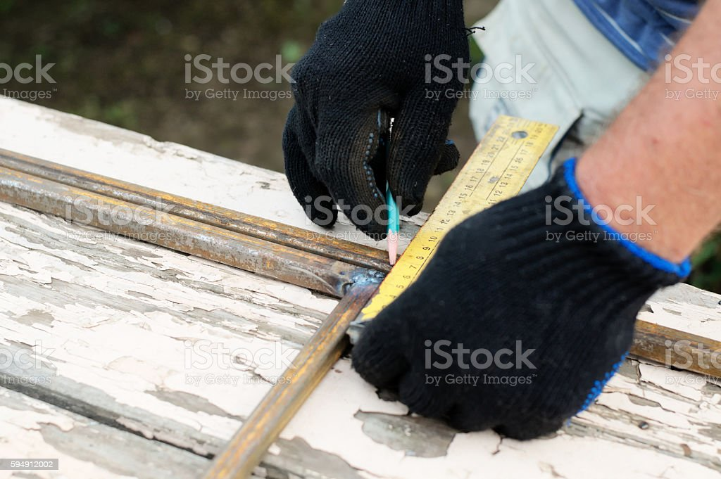 Worker in protective gloves constructing artwork from metal clos stock photo
