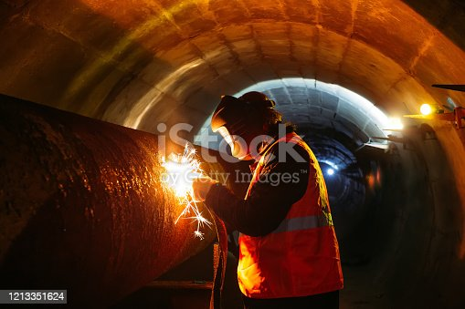 Worker in protective mask welding pipe in tunnel.